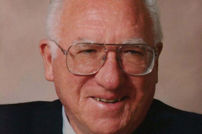 A headshot of a smiling elderly man.