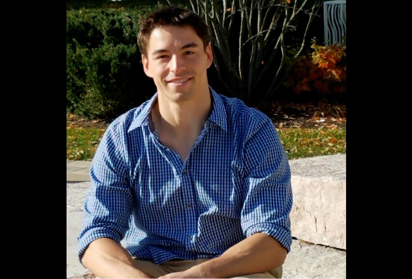 A male graduate student smiles outside.