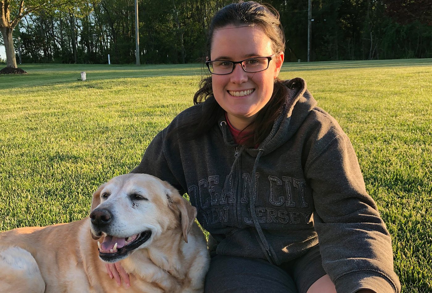A woman smiles beside a yellow lab.